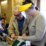Norman Sanders teaching a novice how to turn a Christmas tree decoration.